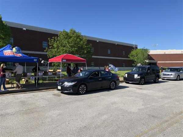 Seniors drive-thru Liberty's parking lot to pick up caps and gowns.