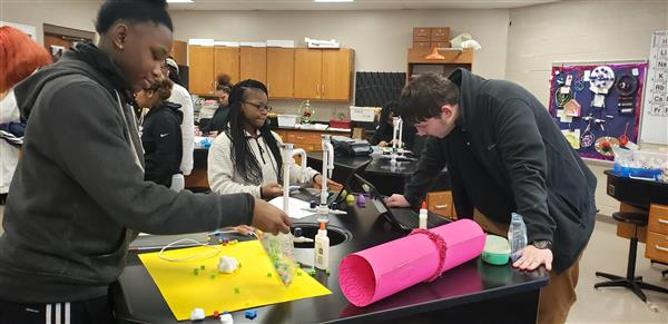 Science students create models of atoms.