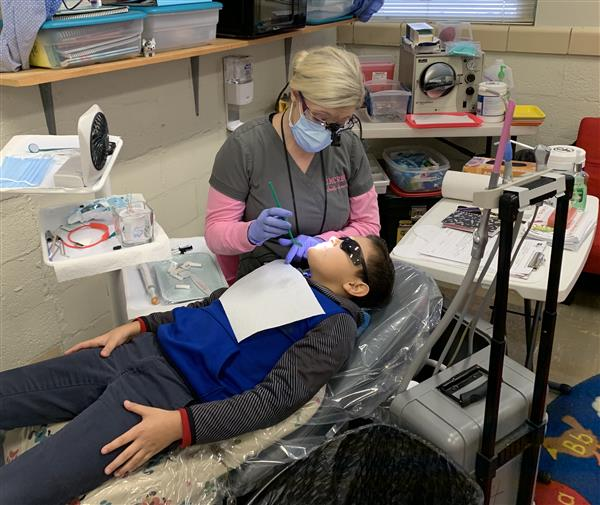 A dental hygienist screens a student for cavities.