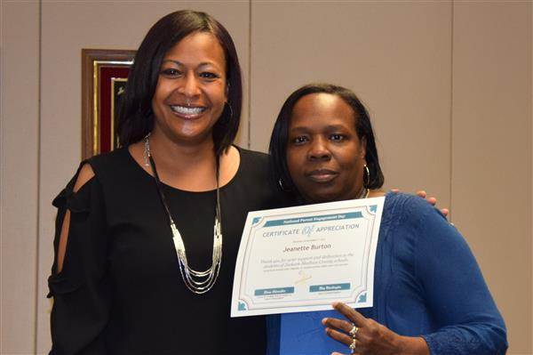 A parent volunteer receives an award on National Parent Engagement Day.