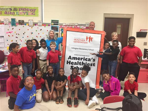 "Arlington students and staff pose with ""America's Healthiest Schools"" award"